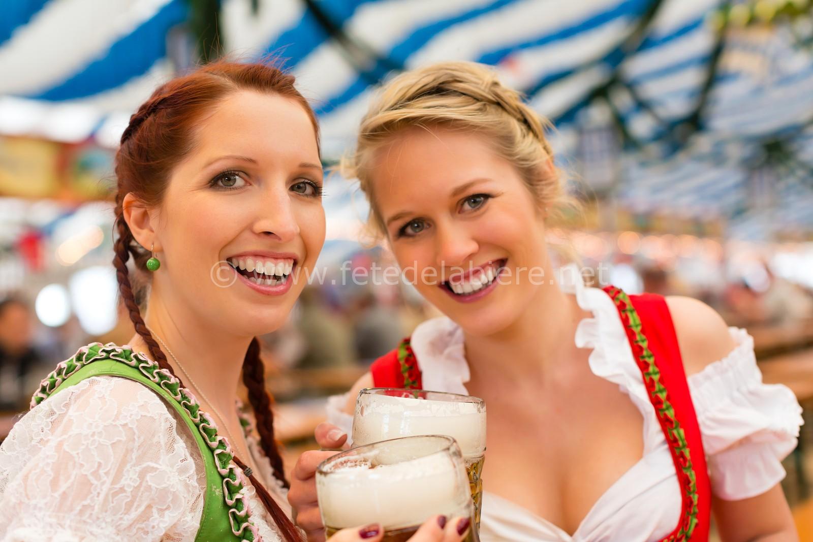 Deux femmes en habits traditionnels bavarois, en dirndl, boit deux Mass de bière.