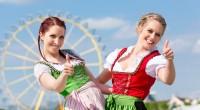 Deux femmes avec le pouce en l'air sont en sécurité devant la grande roue à l'Oktoberfest.